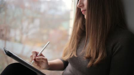 Young woman drawing on digital tablet sitting near window
