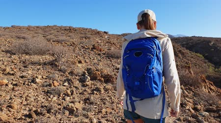 Young woman with backpack hiking in desert hills of volcanic island