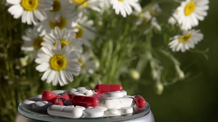 homeopatia : Pills against a green background with flowers