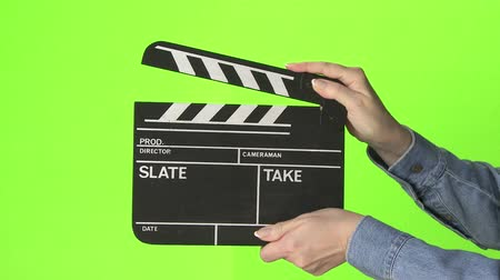 взятие : Woman slating a take with clapper board on green screen