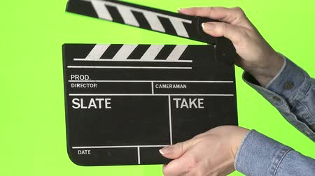 arduvaz : Woman slating a take with clapper board on green screen