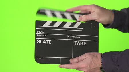 взятие : Man slating a take with clapper board on green screen