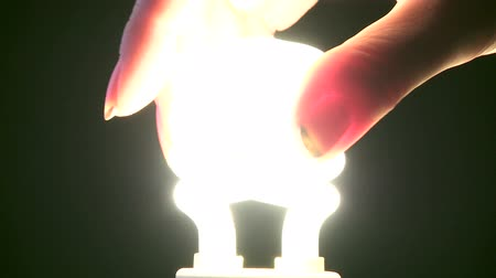 izzók : Female hand turning on new style light bulb