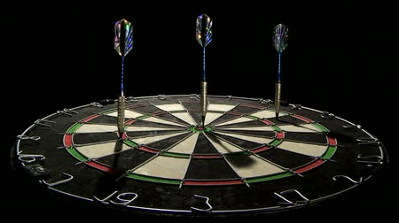 cíle : Three darts hitting the dart board including bull eye low angle