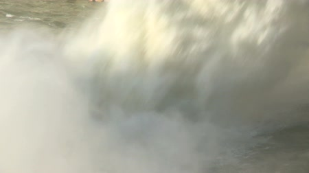 A high volume of falling water splashing into the river