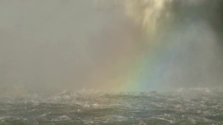 A high volume of falling water splashing into the river with rainbow Vídeos