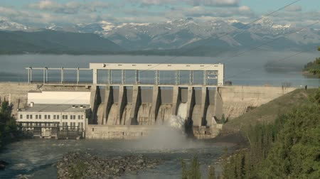 Wide shot of the Ghost Dam and reservoir on the Bow River with the Canadian Rockies in the background. Vídeos