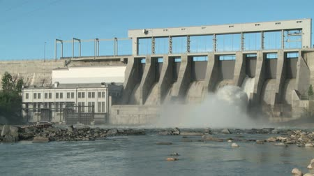 baraj : Wide shot of the Ghost Dam and reservoir on the Bow River with the Canadian Rockies in the background. Stok Video