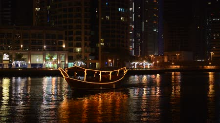 эмираты : The night illumination of Dubai Marina and Dhow boat. It is an artificial canal city, built along a two mile (3 km) stretch of Persian Gulf shoreline. Dubai, UAE