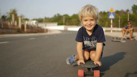deskorolka : Smiling little boy rides sitting on skateboard in slowmotion. Close up shot. Wideo