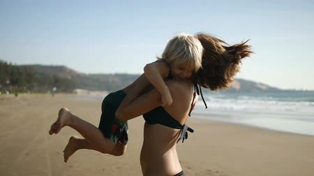 sarılmak : A cute boy runs along the beach into her mother39s arms and they spinning. Slow motion Stok Video