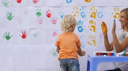 пять : A little cute happy funny child painting color handprints on the white wall with smiling mother together and giving five by hands in print 50fps Стоковые видеозаписи