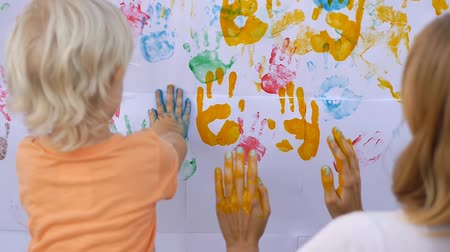 parmak izi : Cute little child painting color handprints on the white wall with mother together. 50fps