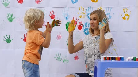 vysoký : Happy little cute child giving five to smiling mother by color paint hands on color handprints background 50fps