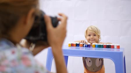 impressão digital : Young photographer shooting a little cute child playing with color paint on colorful handprints background 50fps