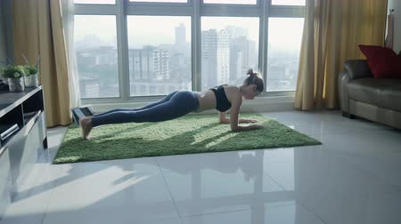 self made : Young woman practicing yoga at home with cityscape background outside the window in the morning. Stretching, working out, fitness, doing exercises on sunrise. Healthy and sport lifestyle. Body care
