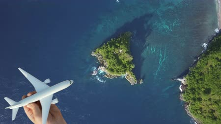 деловые поездки : Travel around the world by air transport, summer vacation concept on nature landscape, blue lagoon background. Scenic aerial view of child hand playing plane, flying above azure water of ocean, island