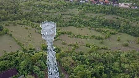 transmitter tower : Aerial view of cell phone communication tower in green nature of city against blue sky. Scenic shot of world telecommunication concept. Stock Footage
