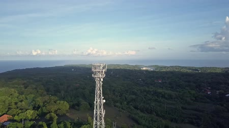 gotículas : Aerial view of cell phone communication tower in green nature of city against blue sky. Scenic shot of world telecommunication concept. Stock Footage