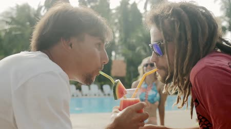 cheers : Summer pool party. Young men in sunglasses drinking fresh juice from one glass. Happy group of friends enjoying the natural drinks together in the resort. Healthy lifestyle. Stock Footage