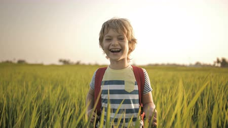 schooler : Smiling child in green grass of rice field on way home from school. Sincere emotion. Positive mood of happy childhood. Enjoying a countryside walk in summer holidays. Laughing at jokes of classmate