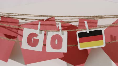 preocupar se : Go word collected by child hand from paper cards with red letters and flag of country Germany. Travel, motivation, sport, text message, business, language education concept.