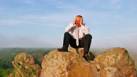 pain free : Businessman in a depression with a headache at sunrise mountain time. 4K 3840x2160 Stock Footage