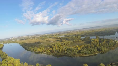 aeroespaço : Flight as bird, with rockings, over river and field with trees. Aerial shot