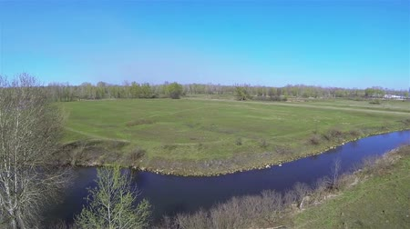 small height : flight over small river and field. Aerial spring landscape