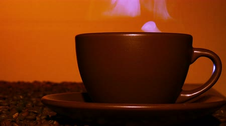bögre : Brown cup of hot coffee or tea with steam in orange tone. Right side. 4K
