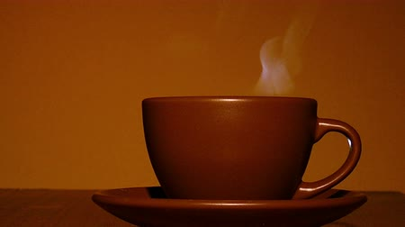 black tea : Brown cup of hot coffee or tea with steam in orange tone. 4K shot
