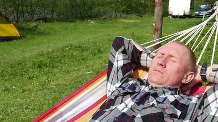 rejtekhely : Adult man traveller with trailer and tent have rest in hammock Stock mozgókép