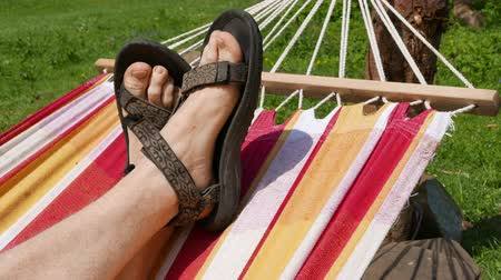 rejtekhely : Foots of man in sandals in hammock close up