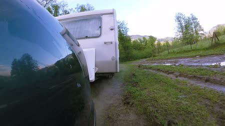 onarılmış : White caravan, trailer go on dirt road after rain. Life on travel