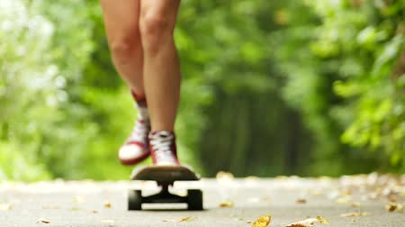 longboarder : teenager girl legs with skateboard in green park. Slow motion Stock Footage