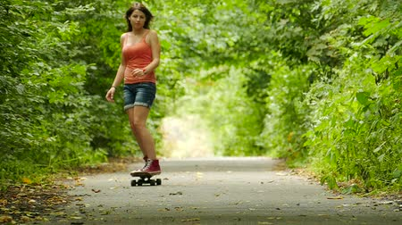 longboarder : Youth culture. Girl with skateboard in summer park. Slow motion 45 seconds.