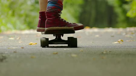 longboarder : teenager girl legs with skateboard in green park move away. Slow motion Stock Footage