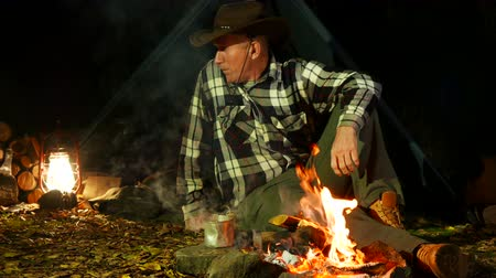 művésziesség : Man in cowboy hat near bonfire goes sleep. Travel life.
