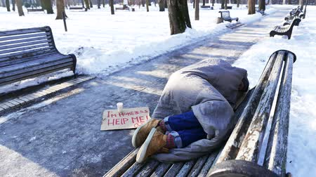 núpcias : 4K.Young Homeless man lie on bench in winter city park. No job, no food, no money Stock Footage