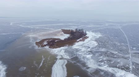 aeroespaço : 4K Aerial. Winter Landscape, fly around small island in frozen sea.