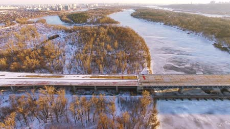 aeroespaço : 4K Aerial. Fly with camera inclination over frozen winter river and bridge Vídeos