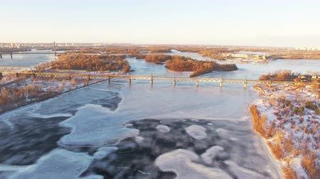 aeroespaço : 4K Aerial. Fly over frozen winter river in city suburb, sunny day.
