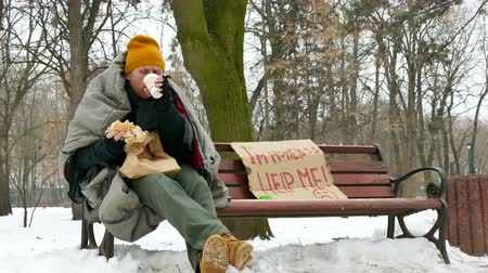 evsiz : 4K. Dinner of homeless hungry man in winter city park, Eating burger close up. Stok Video