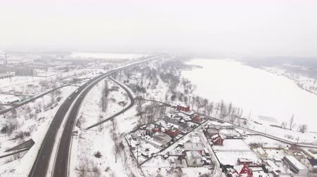 aeroespaço : 4K Aerial. City suburb winter highway with car in foggy cloudy day