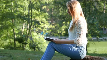 biblia : 4k. Attractive girl open Bible l in sunny park. Christian prayer team shot