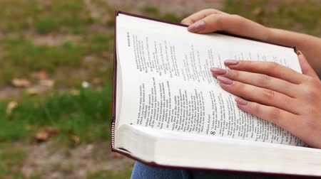 biblia : 4k.Hands and bode of girl with Bible in park. Slider shot