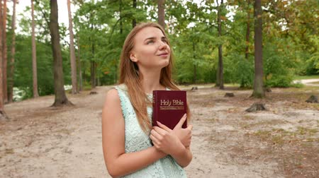 enciclopédia : 4k.Young girl with Bible in park. Christian team intelligent shot