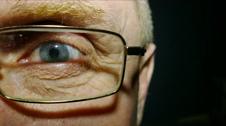 rectus : An eye of the old man wearing spectacles with red capillaries. Macro