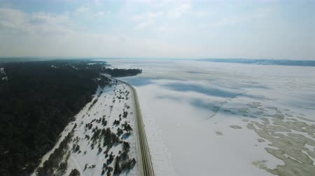 4K Aerial. In the sky over winter frozen sea or lake with costline. Shadow from clouds