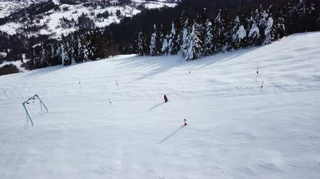 4k.Aerial. Skiers silhouettes on mountain hill. Winter time panorama